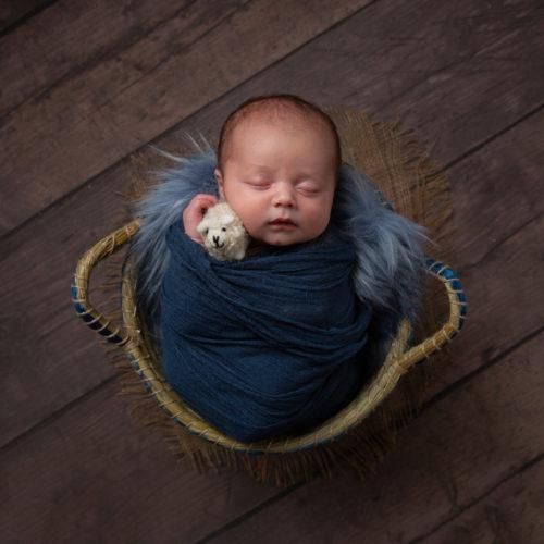 Baby in blue wrap in basket