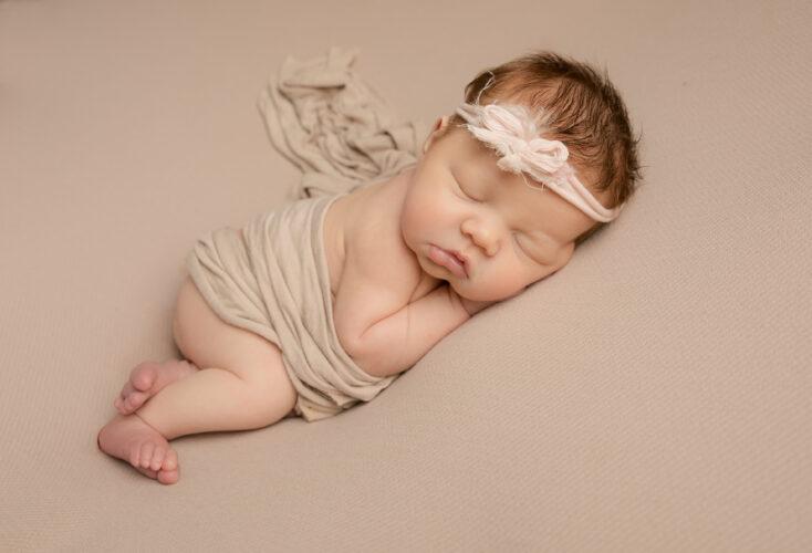 Baby girl on cream blanket